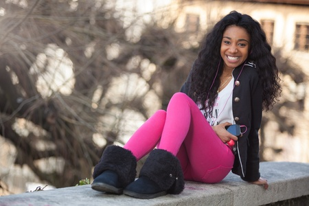 Outdoor of a  portrait happy young african american teenage girl listening to music Stock Photo - 12956971