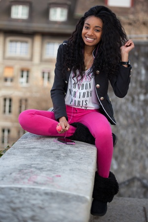 mixed ethnicities: Outdoor of a  portrait happy young african american teenage girl listening to music Stock Photo