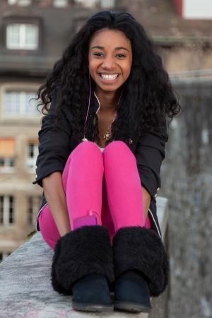 adolescentes chicas: Al aire libre de un retrato feliz de ni�a adolescente africano americano escuchando m�sica