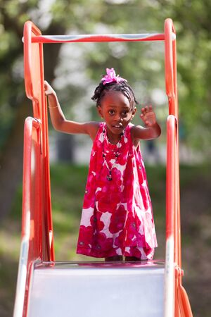 toddler playing: Outdoor Portrait of a cute african american little girl playing at playground