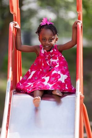 rutsche: Outdoor Portrait von einem h�bschen African American kleinen M�dchen spielen am Spielplatz