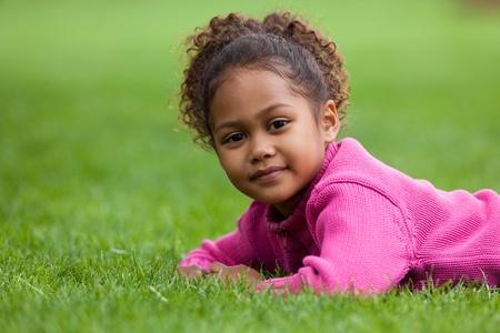 girl lying down: Retrato al aire libre de una ni�a asi�tica africana linda que se acuesta en la hierba