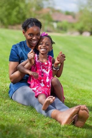 african american mother and daughter: Portrait of a adorable african mother with her daughter in the garden