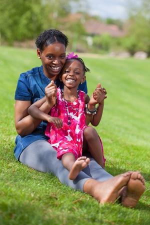 mama e hija: Retrato de una madre africana adorable con su hija en el jard�n