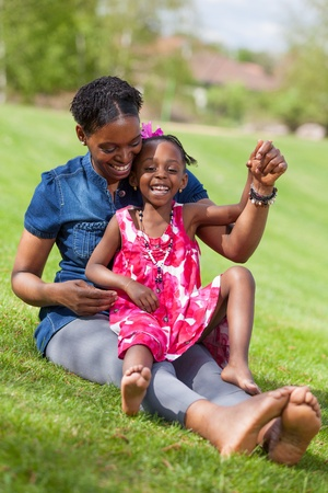 Portrait of a adorable african mother with her daughter in the garden photo