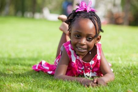 girl lying down: Retrato al aire libre de una linda ni�a afroamericana tumbado en la hierba