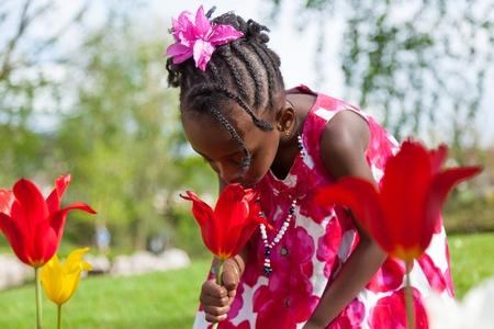 Retrato de un lindo juego africano de American Girl en el jardín Foto de archivo