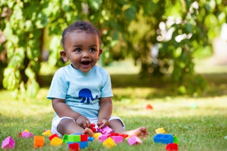 sweet smile: Portrait of a little african american baby boy playing outdoor in the grass Stock Photo