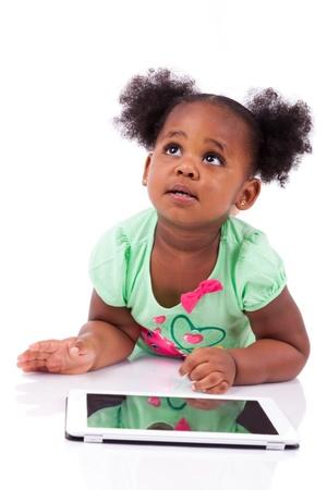 Little Afrikaanse Amerikaanse meisje met behulp van een tablet pc, geïsoleerd op witte achtergrond