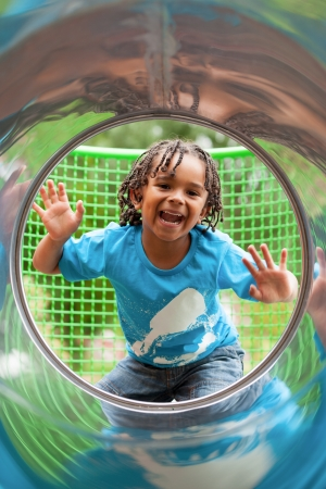 Outdoor portrait of a cute african american little boy playing at playground photo