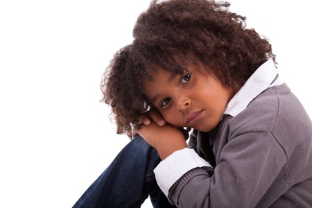 Portrait of an african american little boy sitting on the floor, isolated on white background photo