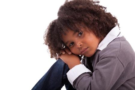 bambini pensierosi: Ritratto di un ragazzo americano africano seduta sul pavimento, isolato su sfondo bianco Archivio Fotografico