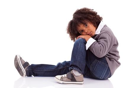 mirada triste: Retrato de un ni�o africano americano sentado en el suelo, aislados sobre fondo blanco Foto de archivo