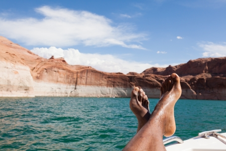 rest day: Feet of a relaxing man lying down on a boat Stock Photo