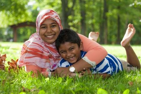 petite fille musulmane: Outdoor portrait de fr�re et soeur jouant indien