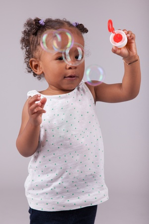 Cute little African American girl playing with soap bubbles Stock Photo - 15762120