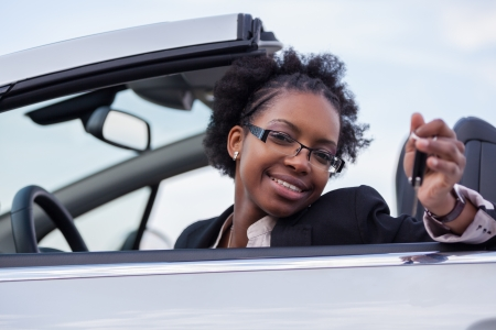 car driver: Young beautiful black woman driver holding car keys driving her new car
