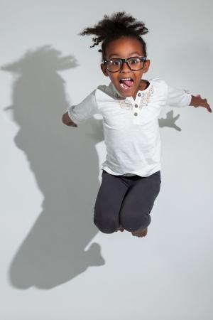 persona saltando: Retrato de joven linda chica que salta africano americano, sobre fondo gris