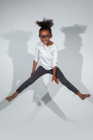 african dance: Portrait of cute Young African American girl jumping, over gray background