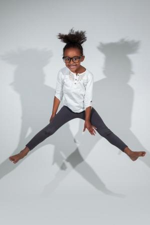 niños danzando: Retrato de joven linda chica que salta africano americano, sobre fondo gris