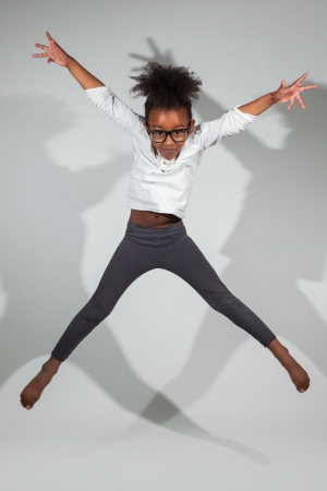 afro caribbean: Portrait of cute Young African American girl jumping, over gray background