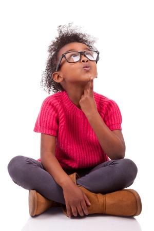 dudando: Retrato de una linda chica joven afroamericana asentada en el suelo