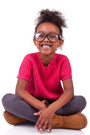 ni�os negros: Retrato de una linda chica joven afroamericana asentada en el suelo