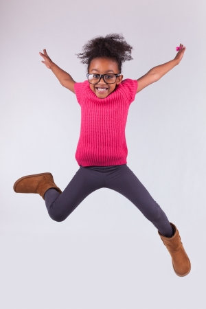 Portrait of cute Young African American girl jumping, over gray background Stock Photo - 16116356