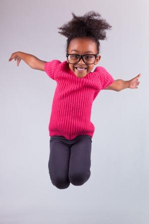 niños bailando: Retrato de joven linda chica que salta africano americano, sobre fondo gris
