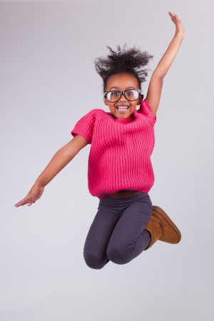 Retrato de joven linda chica que salta africano americano, sobre fondo gris