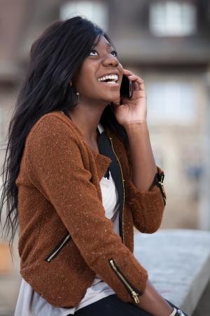 persona llamando: Al aire libre de un retrato feliz joven adolescente negro que usa un tel�fono m�vil Foto de archivo