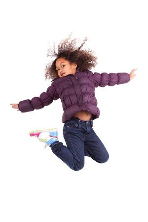 회색 배경 위에 귀여운 젊은 아프리카 아시아 여자 점프의 초상화,