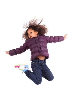 children jumping: Portrait of cute Young African Asian  girl jumping, over gray background