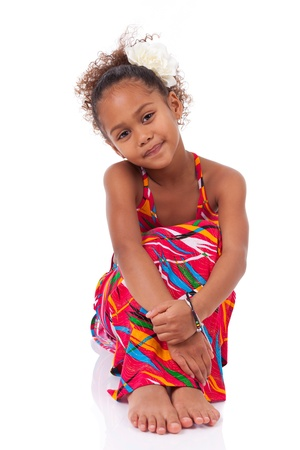 Portrait of a cute young African Asian girl seated on the floor photo
