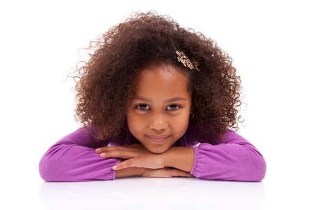 afro caribbean: Portrait of a cute little African Asian girl lying down on the floor