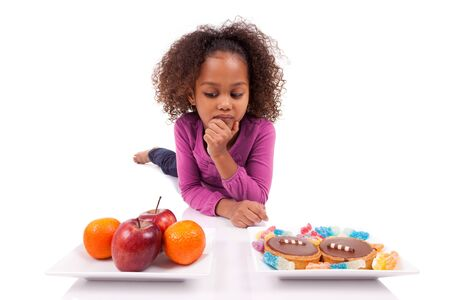 hesitating: Little African Asian girl hesiatating between fruits or  candy,isolated on white background