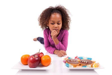 hesitating: Ni�a africana asi�tica hesiatating entre frutas o dulces, aislados en fondo blanco