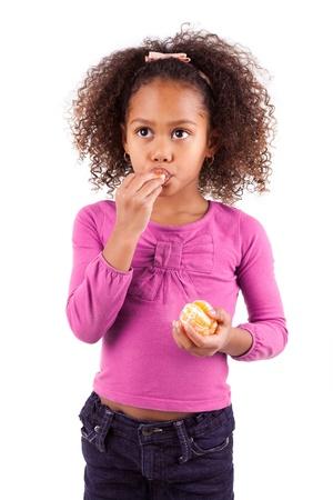 ni�os comiendo: Peque�a muchacha asi�tica africana comiendo una mandarina, aislados en fondo blanco Foto de archivo
