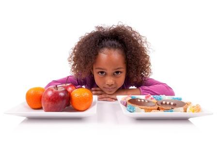 hesitating: Ni�a africana asi�tica dudando entre frutas o dulces, aislados en fondo blanco