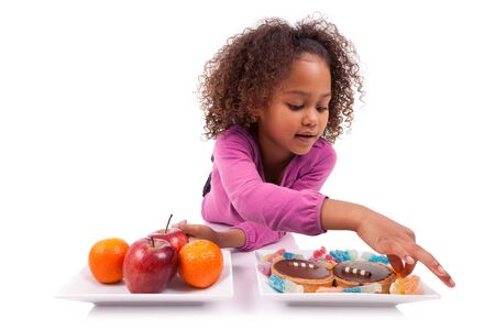 hesitating: Little African Asian girl hesitating between fruits or  candy,isolated on white background