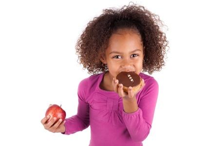 hesitating: Peque�a muchacha asi�tica africana comiendo una torta de chocolate y la celebraci�n de una manzana, aislada en el fondo blanco