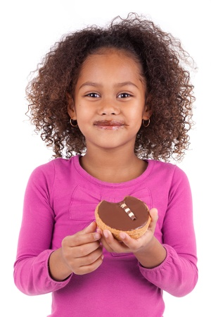 Little African Asian girl eating a chocolate cake, isolated on white background photo