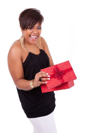 Portrait of a young African American woman opening a gift photo