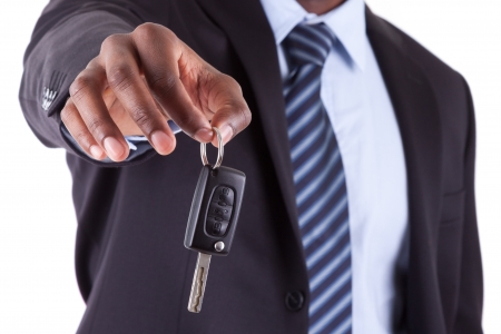 key to success: Young African American businessman holding a car key,isolated on white background