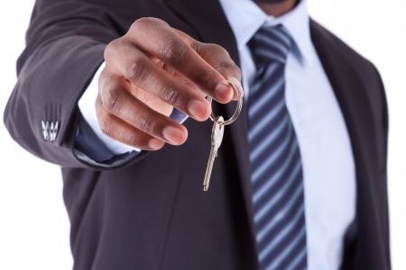 Jonge Afrikaanse Amerikaanse zakenman die een huis sleutel, geïsoleerd op witte achtergrond