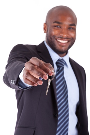 sales agent: Young African American businessman holding a house key, isolated on white background
