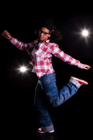 Young African American woman dancing, over black background photo