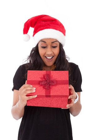 Young African American woman wearing a santa hat opening a gift box, isolated on white background photo