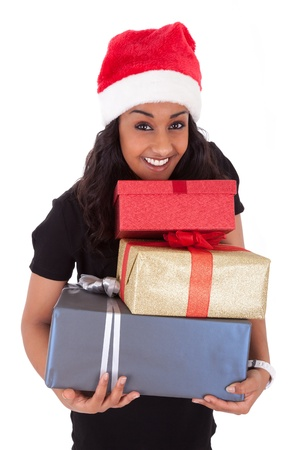 Young African American woman wearing a santa hat holding gift boxes, isolated on white background photo