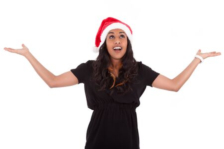 Young African American woman wearing a santa hat looking up, isolated on white background Stock Photo - 16640753